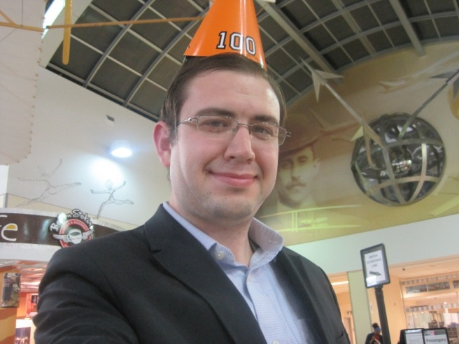 """Paul at the Dayton airport wearing a party hat with """"100"""" written on it."""